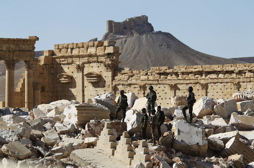 Syrian army soldiers stands on the ruins of the Temple of Bel in the historic city of Palmyra