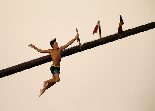 A child competitor grabs a flag as he falls off the