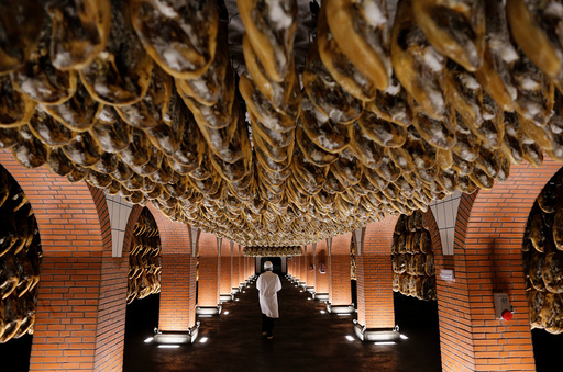 A worker walks in a cellar of cured high-quality Iberian ham legs in Jabugo, southern Spain