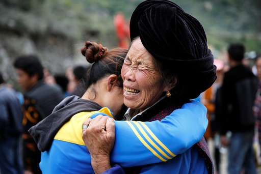 Relatives of victims react at the site of a landslide in the village of Xinmo, Mao County