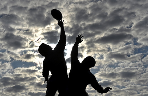 The sun rises behind a statue of rugby players reaching for the ball, outside Twickenham rugby stadium in west London