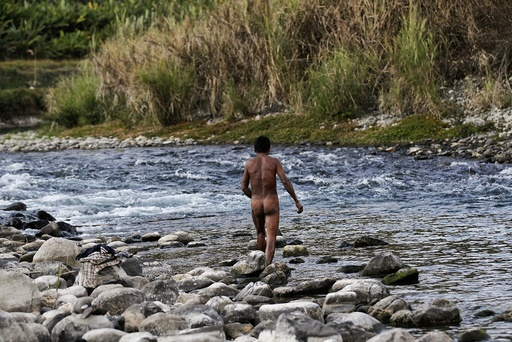 A naked Naga man looks for fish after exploding dynamite in a creek between Donhe and Lahe township in the Naga Self-Administered Zone