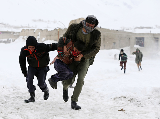 Afghan survivors of an avalanche run to get relief goods distributed by an Afghan army helicopter in the Paryan district of Panjshir