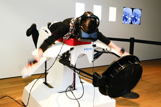 A visitor tries the flight simulator Birdly at the exhibition