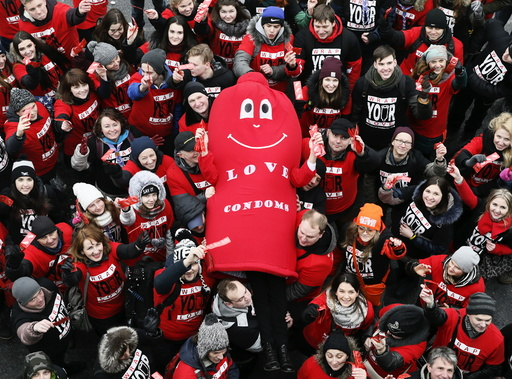 Activists hold a man dressed in a condom costume as they wave hands while marking International Condom Day at a compound of the World War Two museum in Kiev