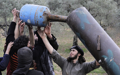 Rebel fighters from Suqour al-Sham Brigade prepare a locally made shell before launching it towards forces loyal to Syria's president Bashar Al-Assad in Idlib countryside