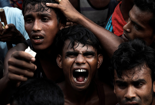 Rohingya refugees scuffle as they wait to receive aid in Cox's Bazar