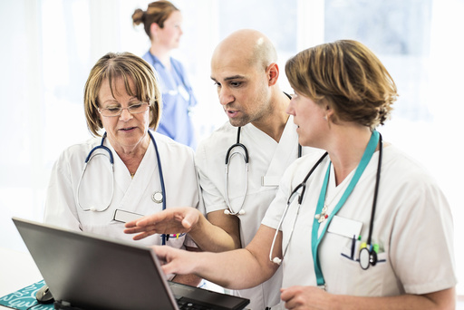 Male doctor explaining to colleagues while looking at laptop in hospital
