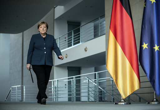 In this Sunday, March 22, 2020 file photo, German Chancellor Angela Merkel arrives for a press conference about coronavirus, in Berlin. German Chancellor Angela Merkel has gone into quarantine after being informed that a doctor who administered a vaccine to her has tested positive for the new coronavirus. With the coronavirus outbreak Merkel is reasserting her traditional strengths, helping reassure the German people and position the country to cope. The new coronavirus causes mild or moderate symptoms for most people, but for some, especially older adults and people with existing health problems, it can cause more severe illness or death. (Michael Kappeler/Pool photo via AP)
