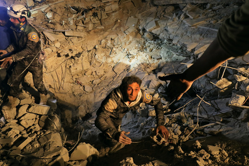 A civil defence member attempts to get out of a site hit at night by an airstrike in Saraqeb, in rebel-held Idlib province, Syria