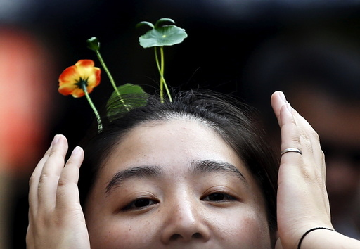 A woman wearing hairpins in the shape of sprouts and flowers makes her way on Nanluoguxiang street in Beijing