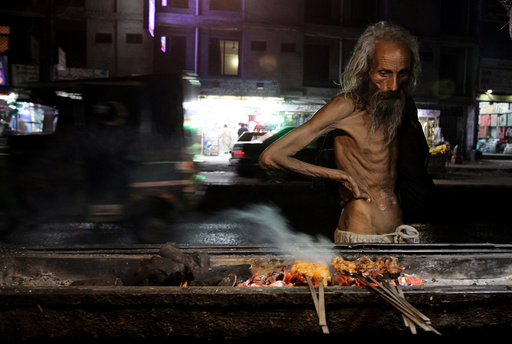 A man looks at kebabs cooking on the street side in Rawalpindi