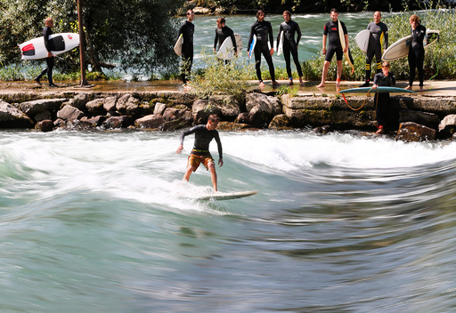 A man surfs on a wave on the Reuss river during sunny weather in the town of Bremgarten