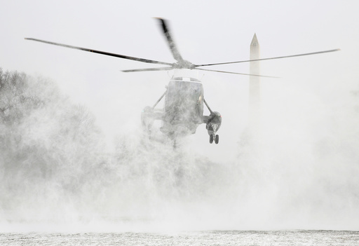 Marine One blows up a cloud of snow as it lands on the South Lawn of the White House in Washington.