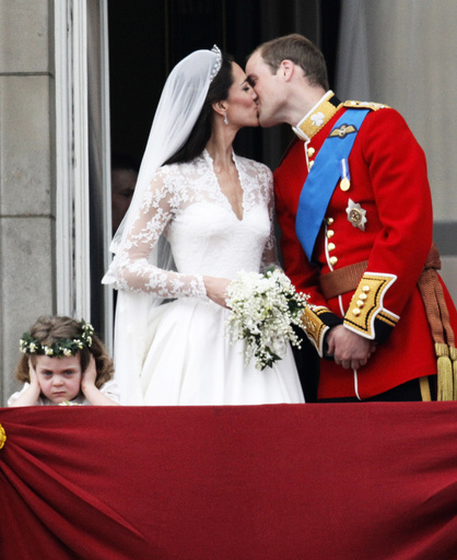 Britain's Prince William and his wife Catherine, Duchess of Cambridge, kiss as they stand next to bridesmaid Grace van Cutsem on the balcony at Buckingham Palace after their wedding in Westminster Abbey, in central London
