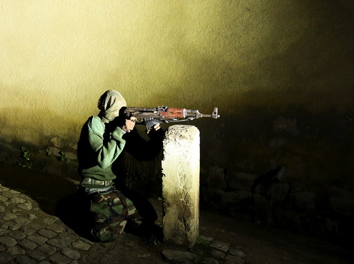 An armed vigilante holds an AK-47 rifle in the center Bujumbura, Burundi