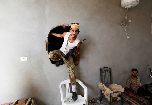 A fighter from Libyan forces allied with the U.N.-backed government climbs out of a hole during a fight with Islamic State in neighbourhood Number Three in Sirte