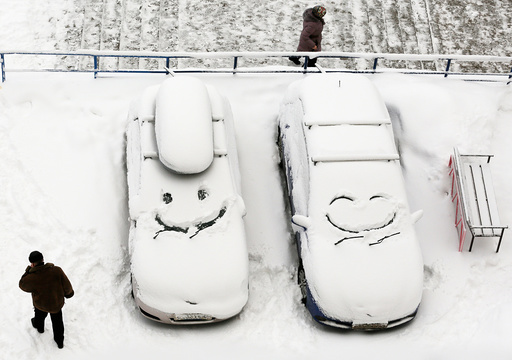 People walk past cars with faces which are scrawled on windscreens covered with snow after snowfall in Krasnoyarsk