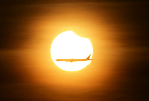 An aeroplane flies past the sun as it goes into a partial solar eclipse in Singapore