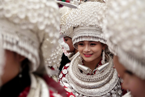 Ethnic Miao women wearing traditional costumes take part in a parade during the traditional Lusheng (reed-pipe wind instrument) festival in Gulong