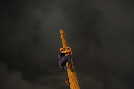 A man climbs up a wooden pole during Maslenitsa celebrations at Gorky park in Moscow