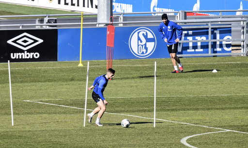 Due to the coronavirus outbreak at most two players of the German first division, Bundesliga, soccer club Schalke 04 exercise together to keep distance during the training on the club's training ground in Gelsenkirchen, Germany, Tuesday, April 1, 2020. The German Football League (DFL) announced all matches will be suspended until at least 30th April due to the ongoing coronavirus pandemic. The new coronavirus causes mild or moderate symptoms for most people, but for some, especially older adults and people with existing health problems, it can cause more severe illness or death. (AP Photo/Martin Meissner)