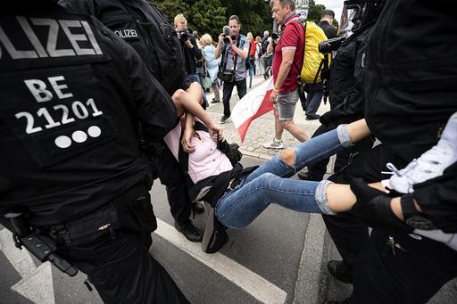 Politiet pågriper en demonstrant i Berlin søndag, da flere tusen demonstrerte mot koronarestriksjoner i den tyske hovedstaden. Foto: Fabian Sommer / DPA via AP / NTB