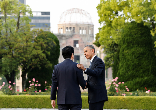 U.S. President Barack Obama puts arm around Japanese PM Abe after they laid wreaths in front of cenotaph as the atomic bomb dome is background at Hiroshima Peace Memorial Park in Hiroshima, Japan