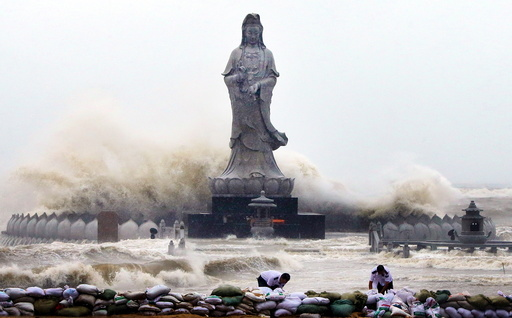 People set up sand bags to reinforce an embankment in front of an Avalokitesvara Bodhisattva statue as waves brought by Typhoon Dujuan slam the coastline in Quanzhou