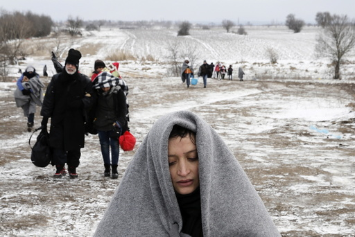 Migrants walk through a frozen field after crossing the border from Macedonia, near the village of Miratovac, Serbia