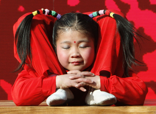A young acrobat performs during a cultural show to celebrate Lunar New Year at a temple fair in Beijing