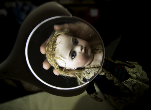 A worker examines a French bisque doll at the Vectis auction house in Stockton-on-Tees