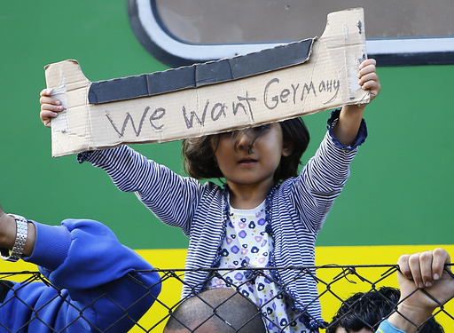 A young migrant girl holds up a sign during a protest in front of a train at Bicske railway station