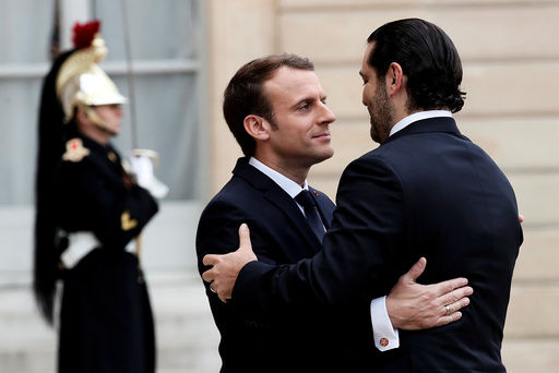 French President Emmanuel Macron and Saad al-Hariri, who announced his resignation as Lebanon's prime minister while on a visit to Saudi Arabia, embrace in the courtyard of the Elysee Palace in Paris