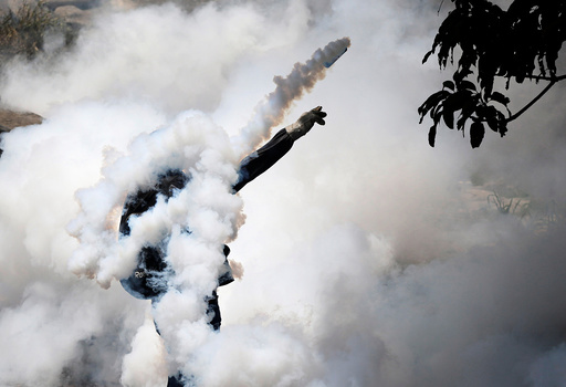 A demonstrator throws back a tear gas grenade while clashing with riot police during the so-called