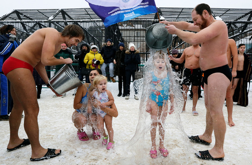 Visitors watch as members of local winter swimmers club pour buckets of cold water over their daughters during celebration of Polar Bear Day at Royev Ruchey zoo in Krasnoyarsk