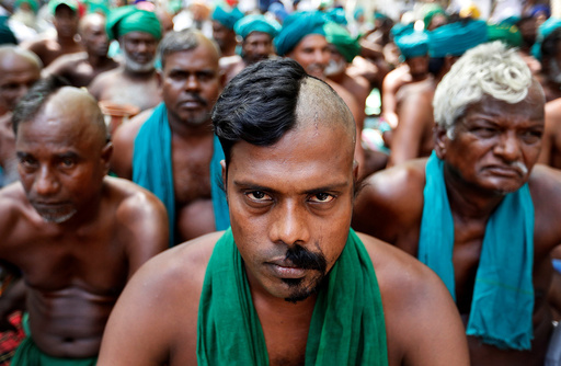 Farmers from the southern state of Tamil Nadu pose half shaved during a protest demanding a drought-relief package from the federal government, in New Delh