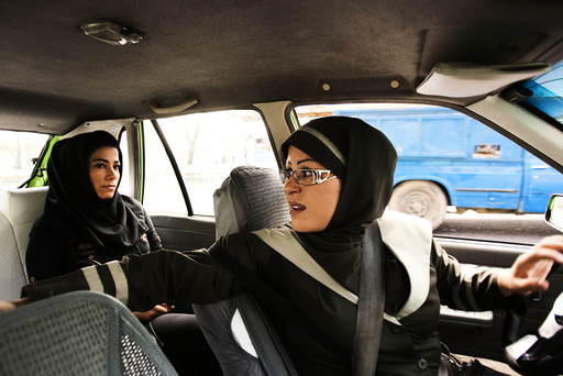 A female taxi driver is seen fetching a passenger in Tehran