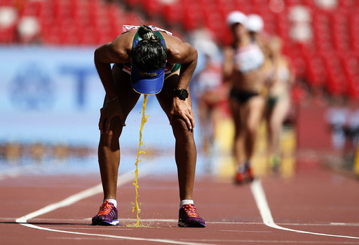 Cisiane Lopes of Brazil vomits after competing in the women's 20 km race walk final during the 15th IAAF World Championships at the National Stadium in Beijing,