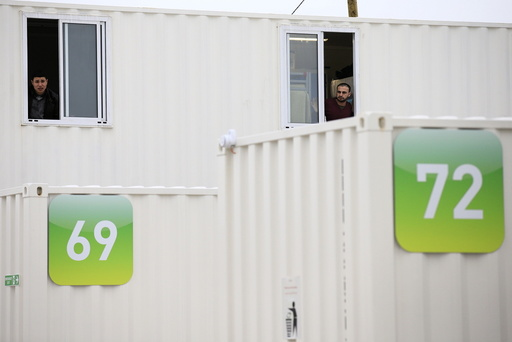 Migrants look out of the windows of a shipping container converted into a home at a state-run shelter near Calais, northern France