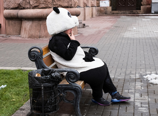 A man dressed as a panda rests and smokes in between posing for pictures with tourists in central Kiev