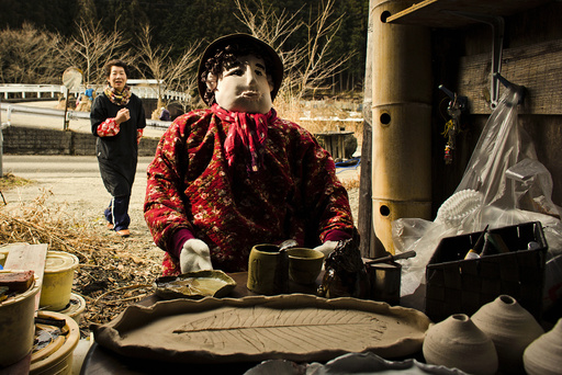 Tsukimi Ayano walks towards a scarecrow, which she made as a likeness of herself, in the mountain village of Nagoro