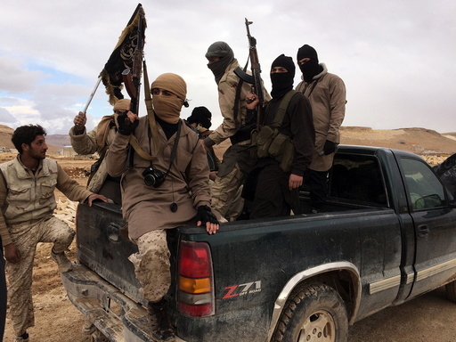 Al Qaeda-linked Nusra Front fighters carry their weapons on the back of a pick-up truck during the release of Lebanese soldiers and policemen in Arsal, eastern Bekaa Valley, Lebanon