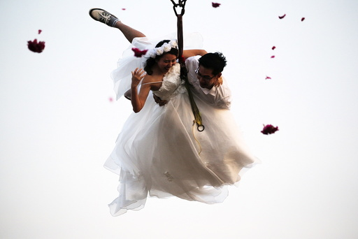 Bride Duangreuthai and groom Kasemsak fly while attached to cables during a wedding ceremony ahead of Valentine's Day at a resort in Ratchaburi province
