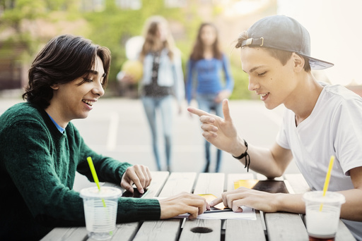 Happy male teenagers using digital tablet at table outdoors