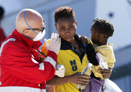 A rescue worker helps a woman with her son as they disembark the Italian naval vessel Cigala, in the Sicilian harbour of Augusta