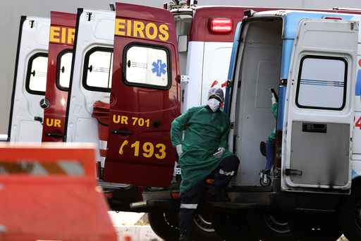 Helsearbeidere tar en pause etter å ha fraktet en pasient med mistenkt covid-19-smitte til et sykehus i Brasilia som spesialiserer seg på behandling av koronapasienter. Brasil er det hardest rammede landet i Latin-Amerika. I regionen er det nå registrert over fem millioner koronatilfeller. Foto: Eraldo Peres / AP / NTB scanpix