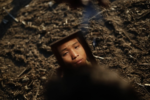 A Naga boy looks at himself in a mirror as he gets a hair cut in Yansi village, Donhe township in the Naga Self-Administered Zone