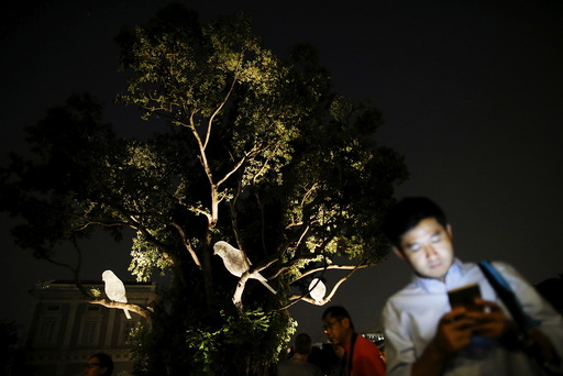 People walk past an art installation of three bird sculptures, Le Desir Et La Menace, by French artist Cedric le Borgne during a media preview of the Singapore Night Festival in Singapore
