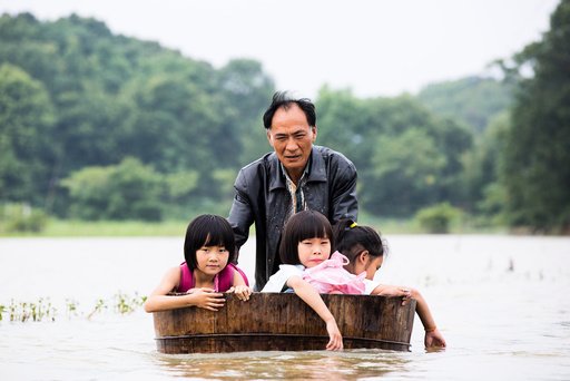 A man pushes a tub carrying children as he gets them back home after school at a flooded area in Duchang